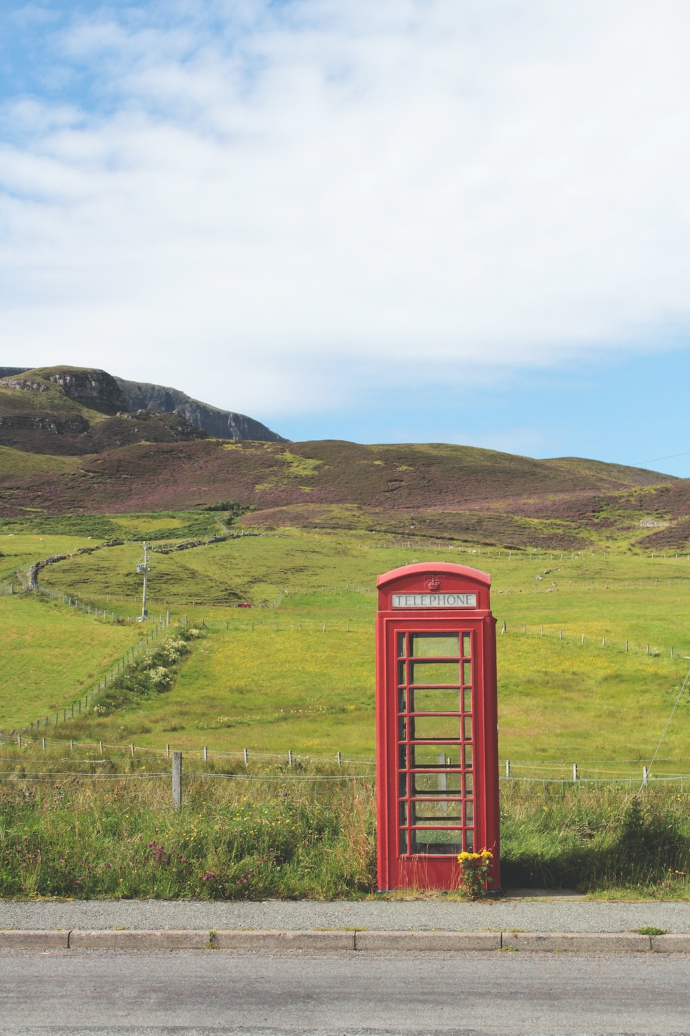 red telephone booth on green grass field during daytime