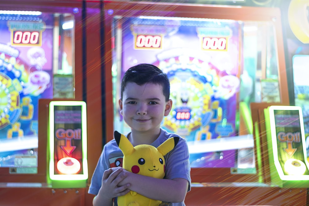boy in blue and white polo shirt holding yellow plush toy