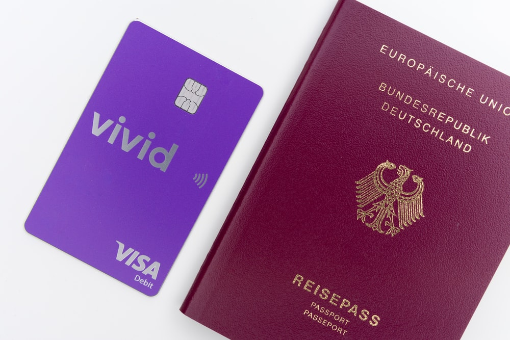purple and gold passport on white surface