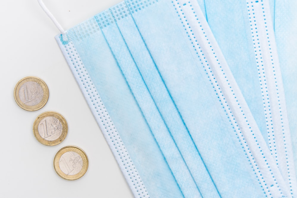 silver round coins on white textile