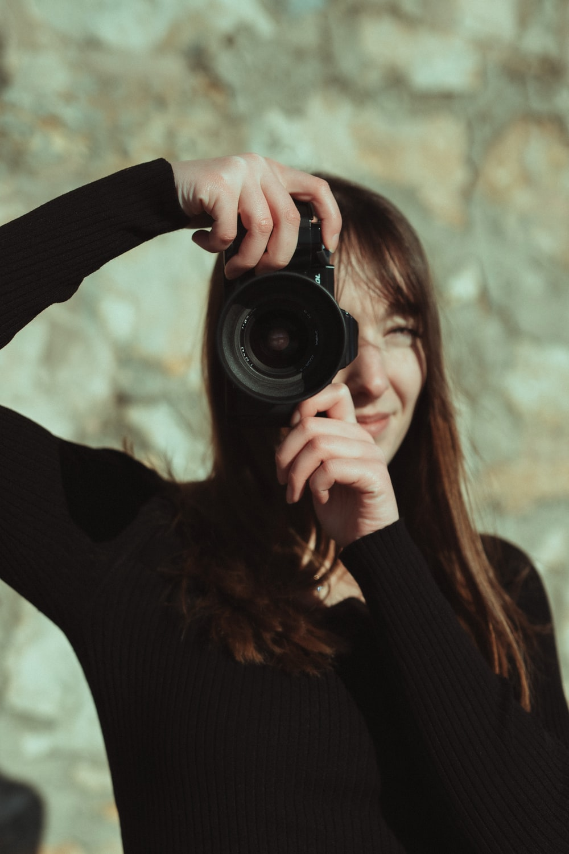 woman in black long sleeve shirt holding black camera