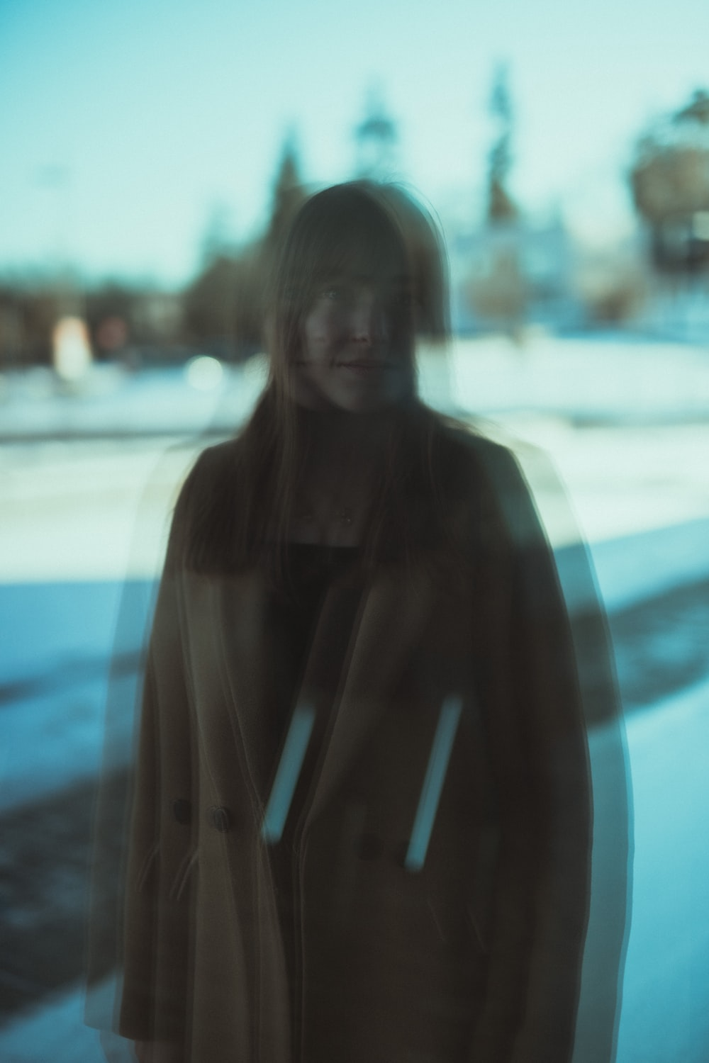 woman in black hoodie standing on snow covered ground during daytime