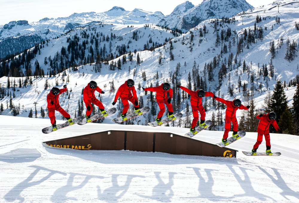 group of people in red jacket and pants standing on snow covered ground during daytime