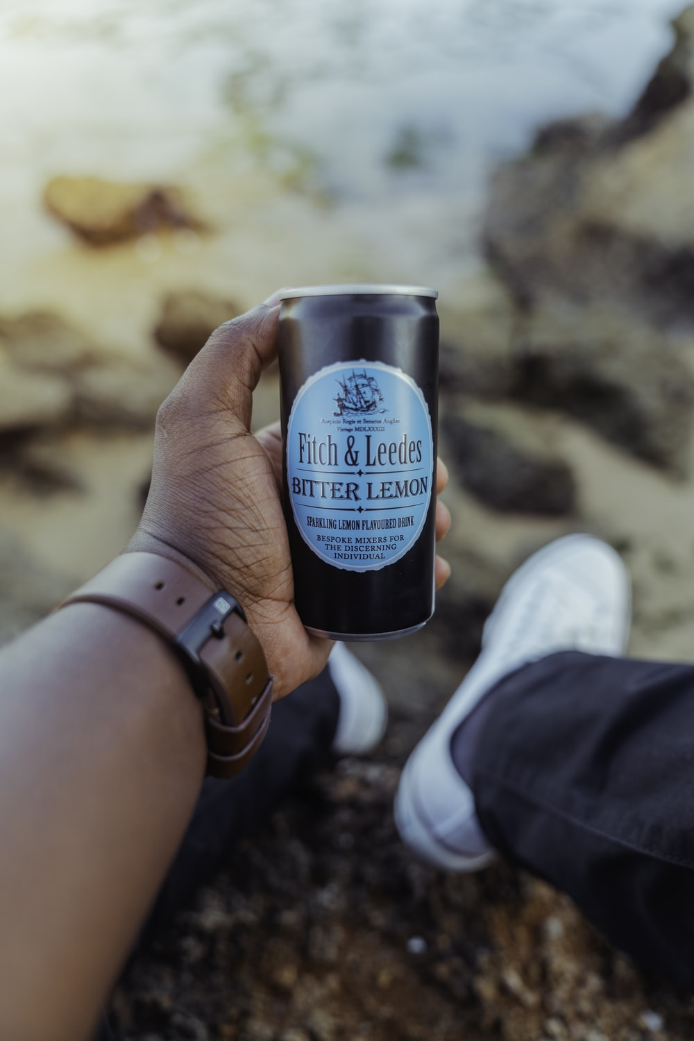 person holding blue and black the body shop bottle