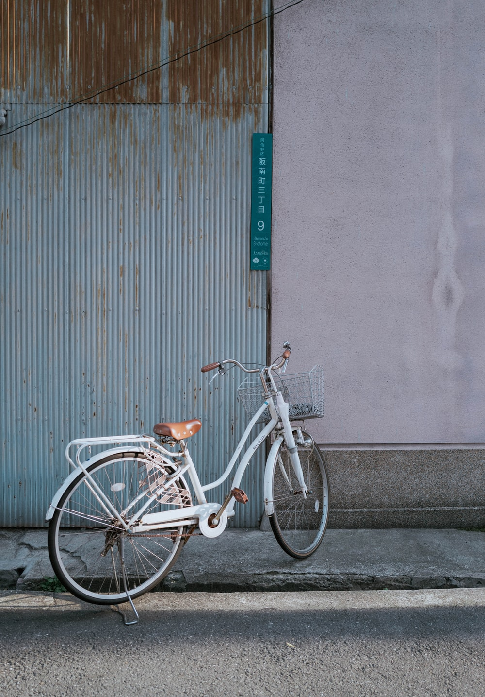 white city bike parked beside gray wall