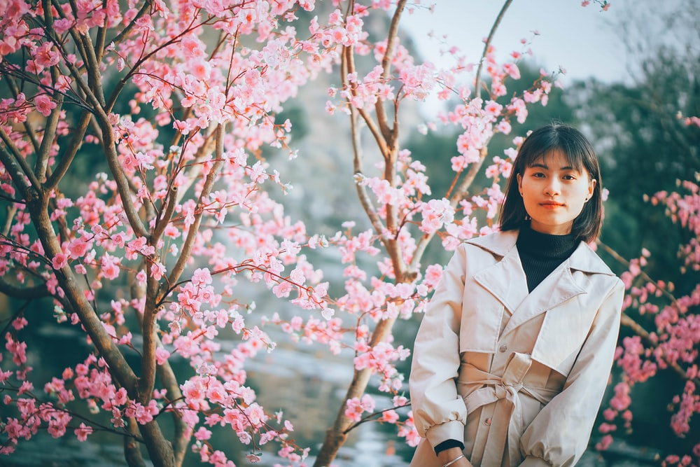 woman in beige coat standing beside pink cherry blossom tree during daytime