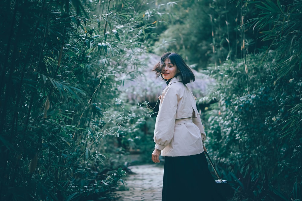 woman in white long sleeve shirt and black skirt standing in the middle of green plants