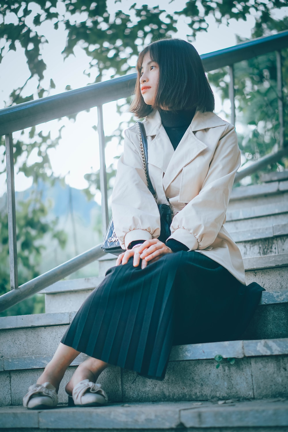 woman in white coat sitting on stairs