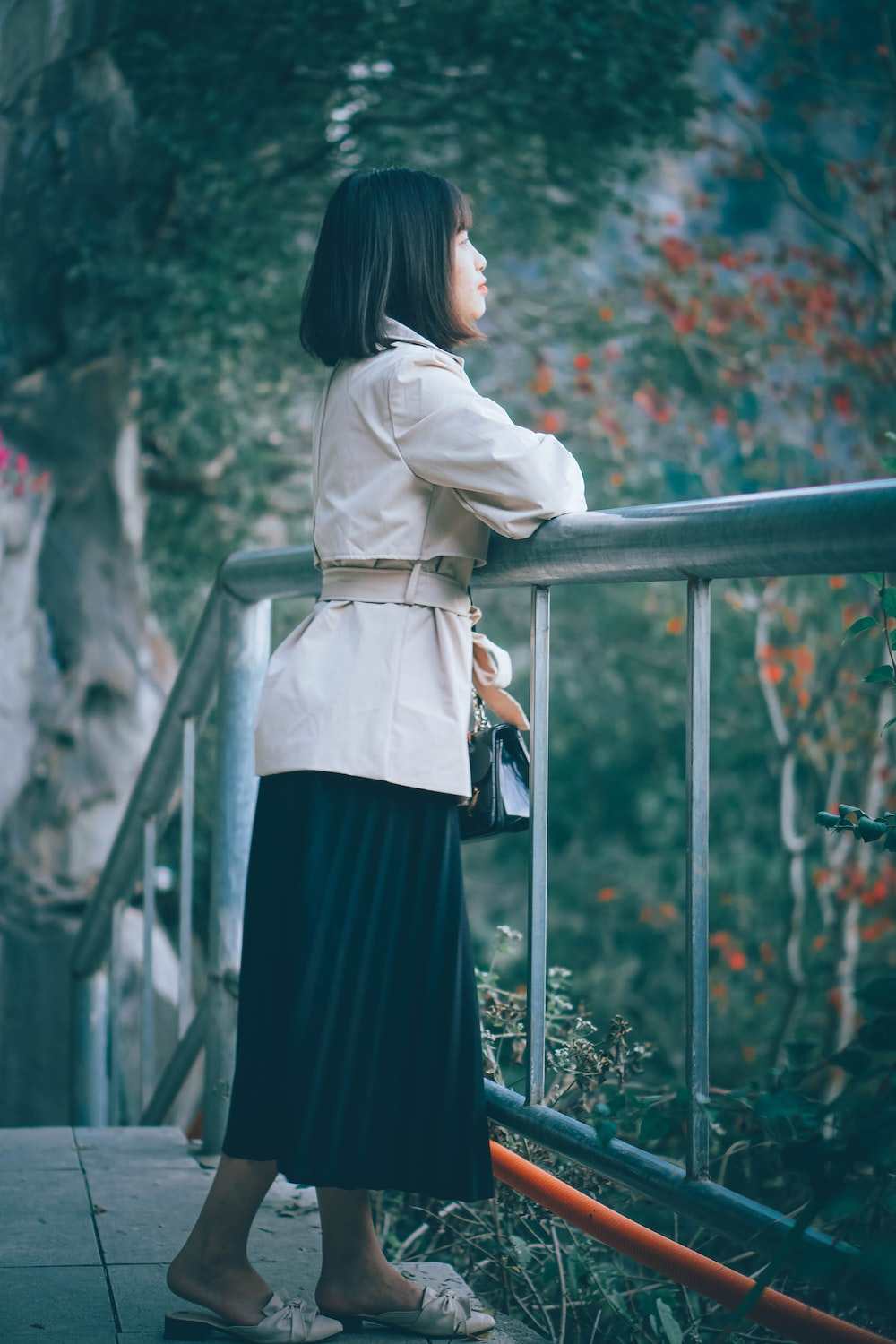 woman in white long sleeve shirt and black skirt standing on gray metal railings during daytime