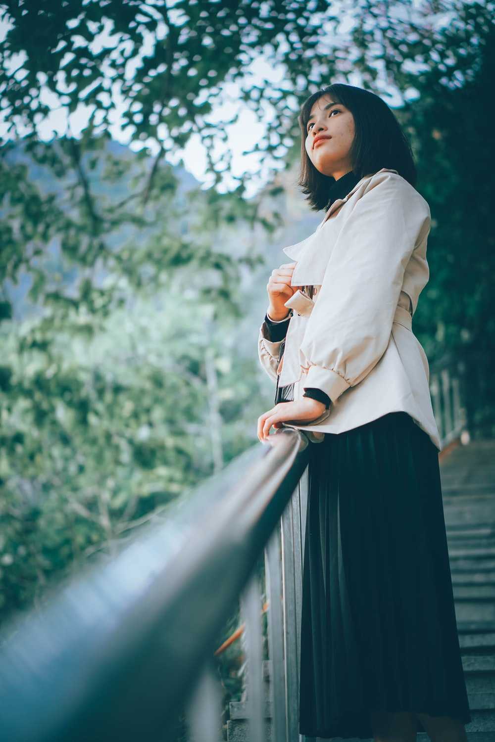 woman in white long sleeve shirt and black skirt standing on bridge during daytime