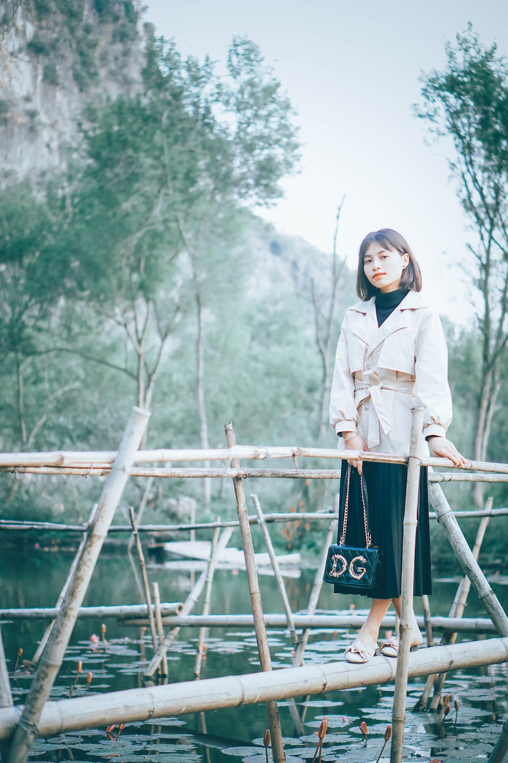 woman in white coat standing on brown wooden bridge during daytime