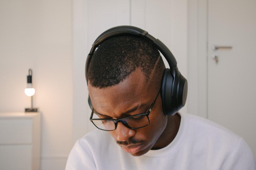 man in white crew neck shirt wearing black headphones