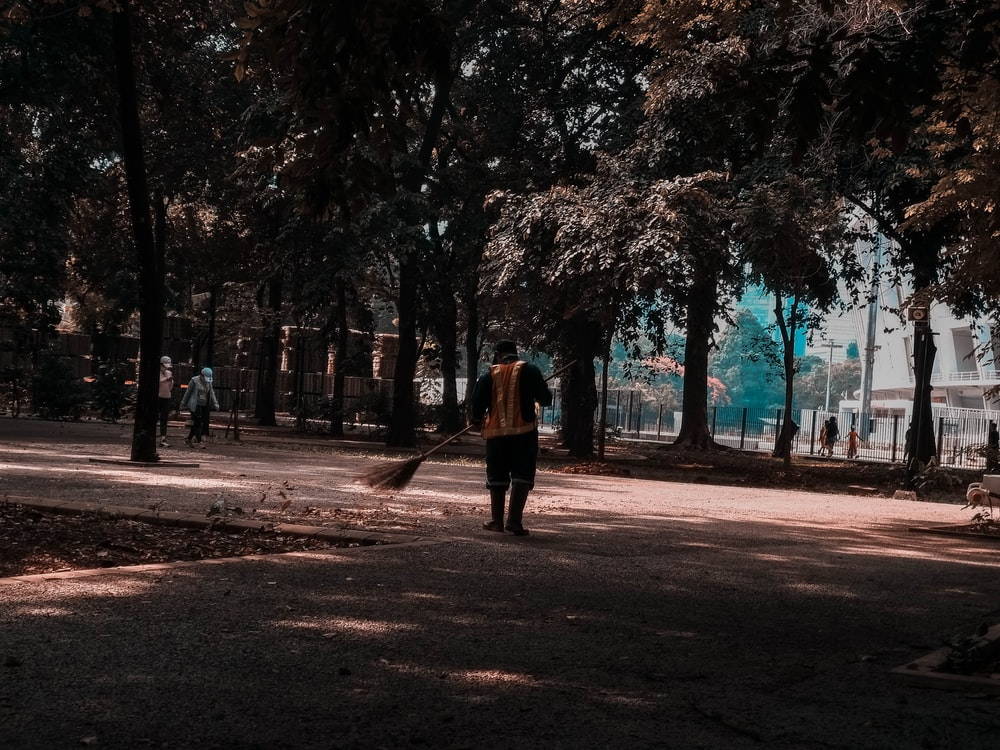 woman in brown coat walking on pathway surrounded by trees during daytime