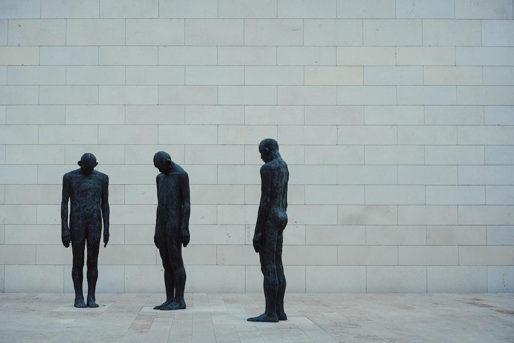 3 black statue standing on white concrete floor