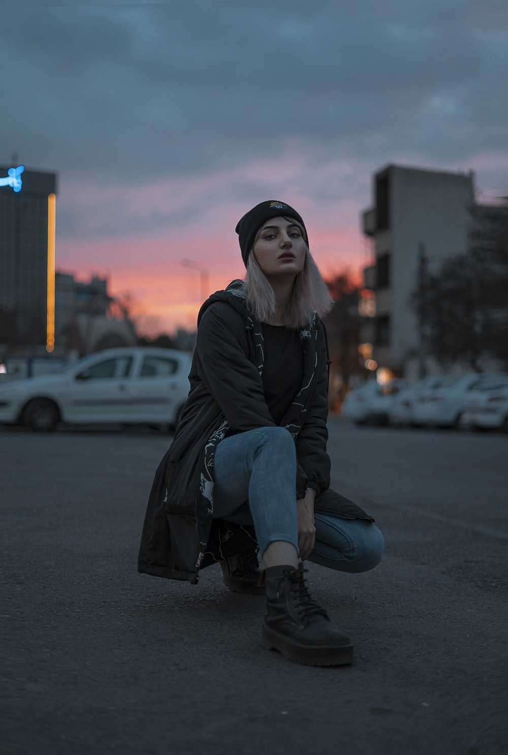 woman in black jacket and blue denim jeans sitting on road during daytime