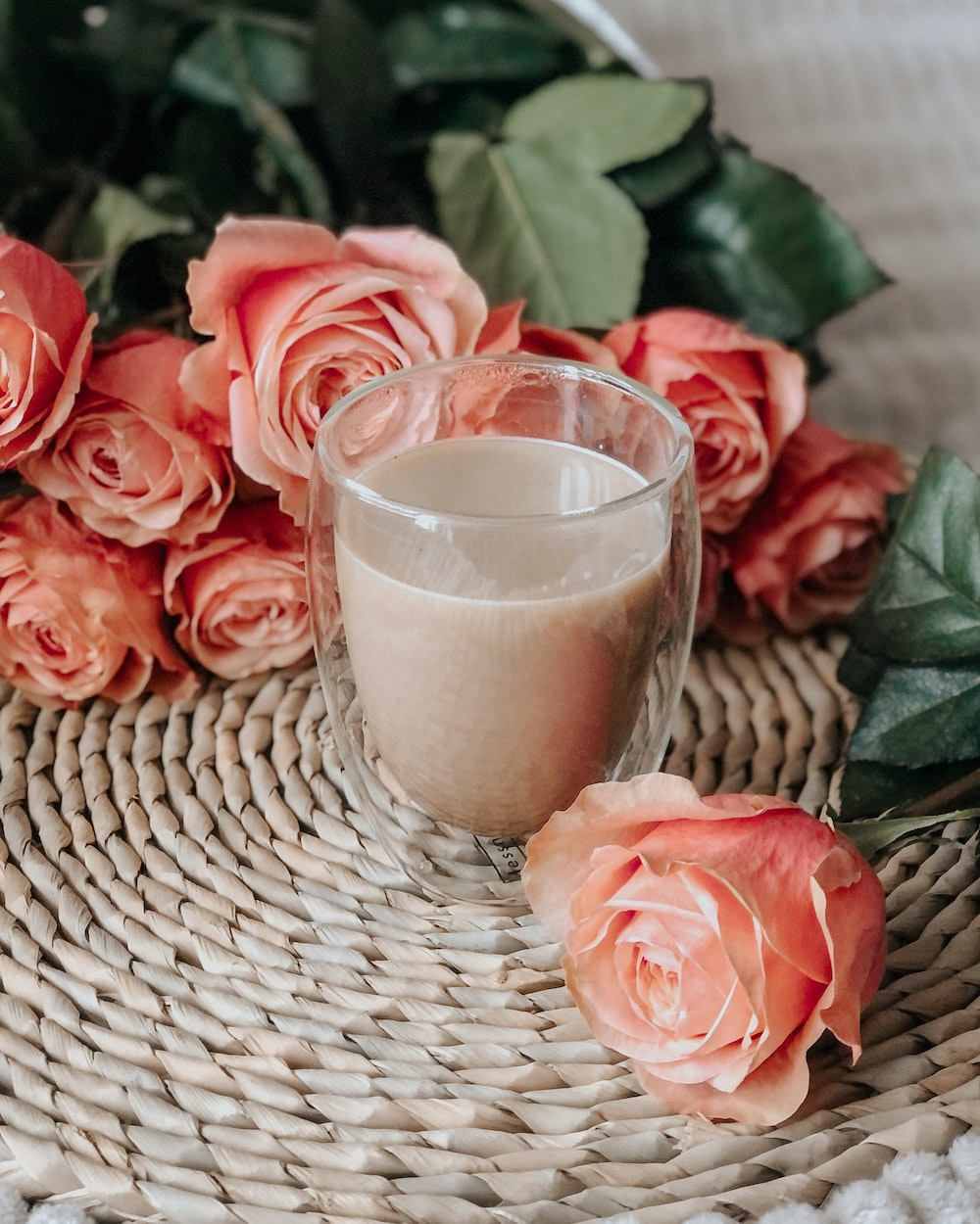 pink roses beside clear drinking glass on brown woven round table