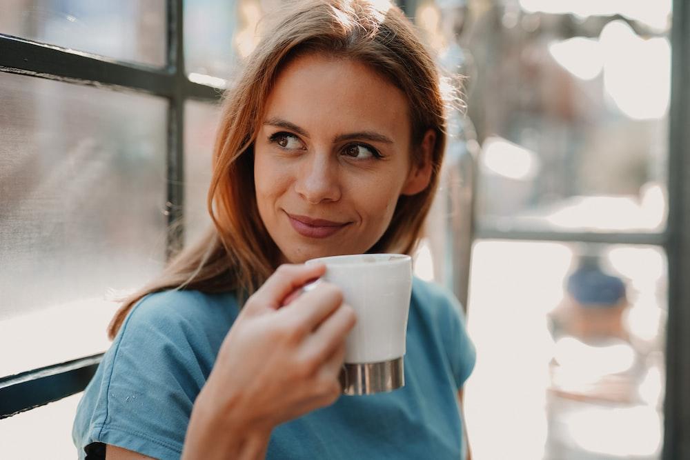 woman in blue long sleeve shirt holding white ceramic mug
