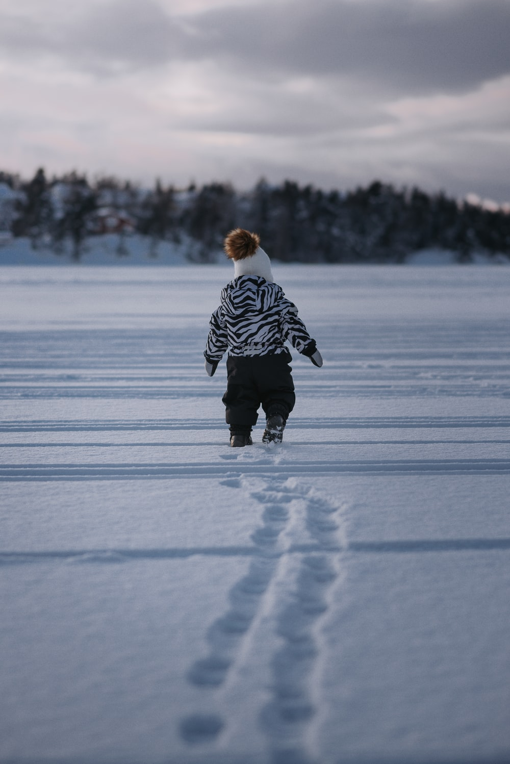 child in black and white striped jacket walking on snow covered ground during daytime