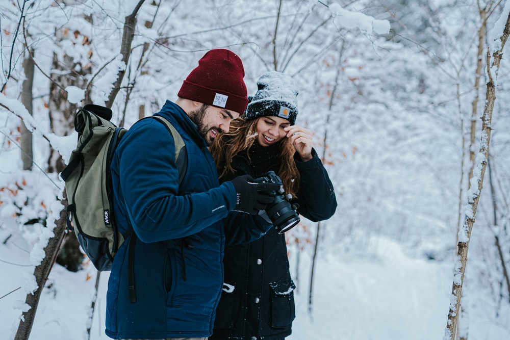 woman in black jacket taking photo of snow covered ground