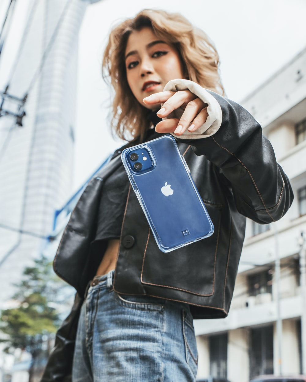 woman in black leather jacket holding blue iphone case