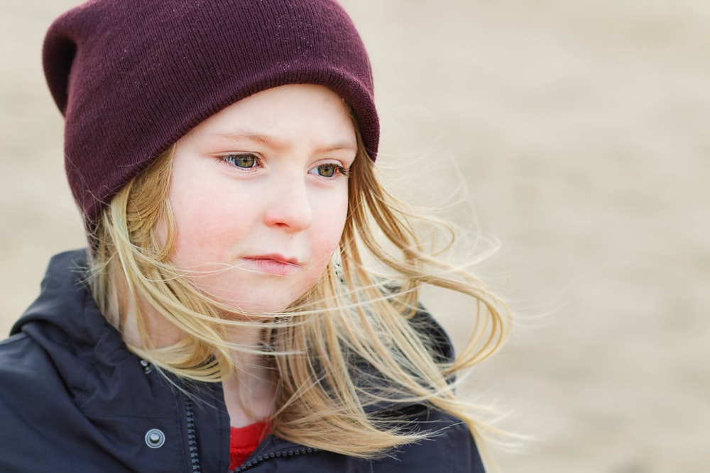 girl in red knit cap and black jacket