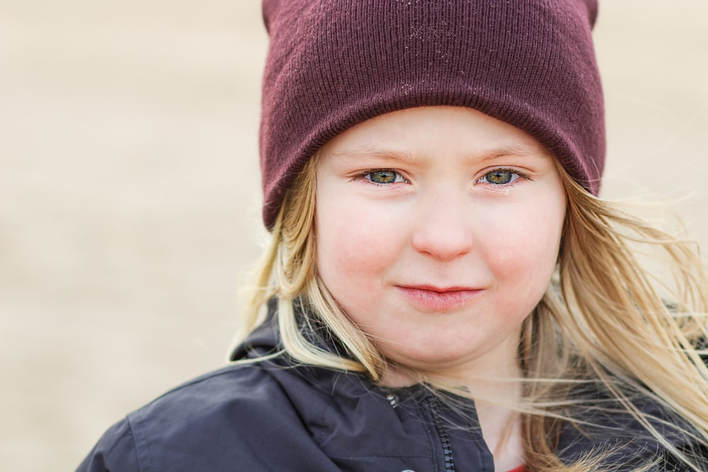 girl in black jacket wearing red knit cap