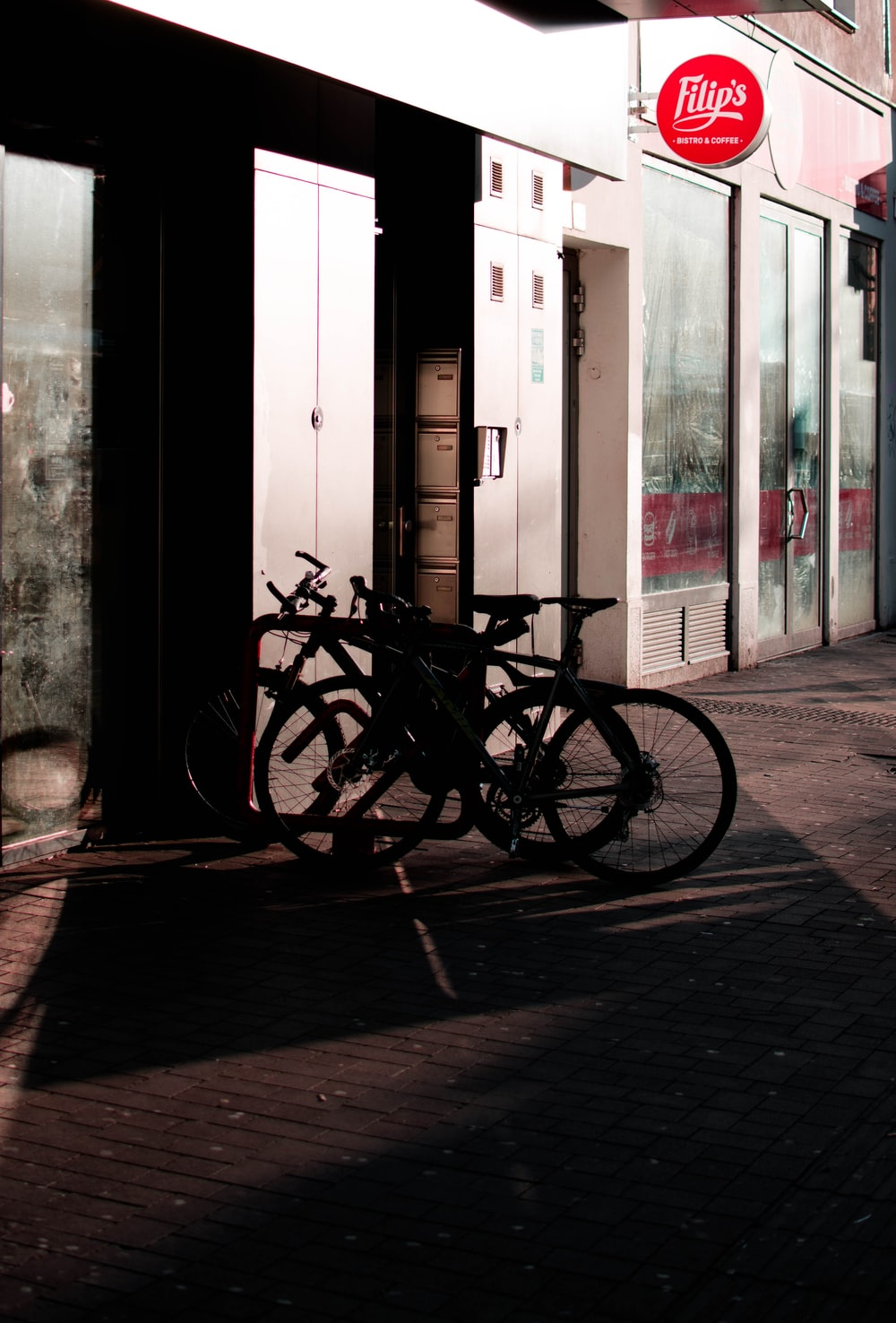 black bicycle parked beside white wooden door