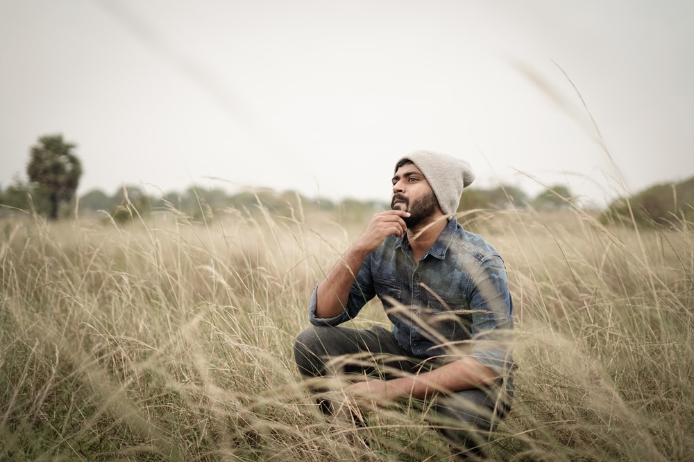 man in blue denim jacket and gray hat sitting on brown grass field