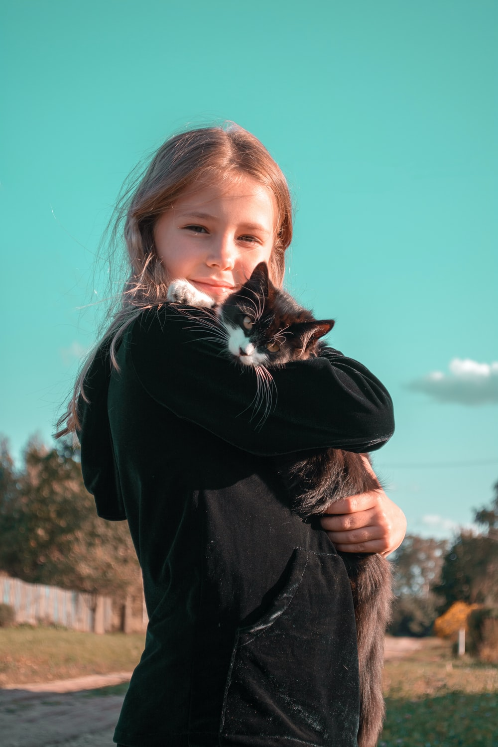 woman in black long sleeve shirt holding white and black cat