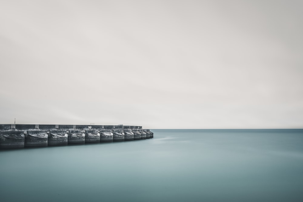gray concrete dock on body of water during daytime