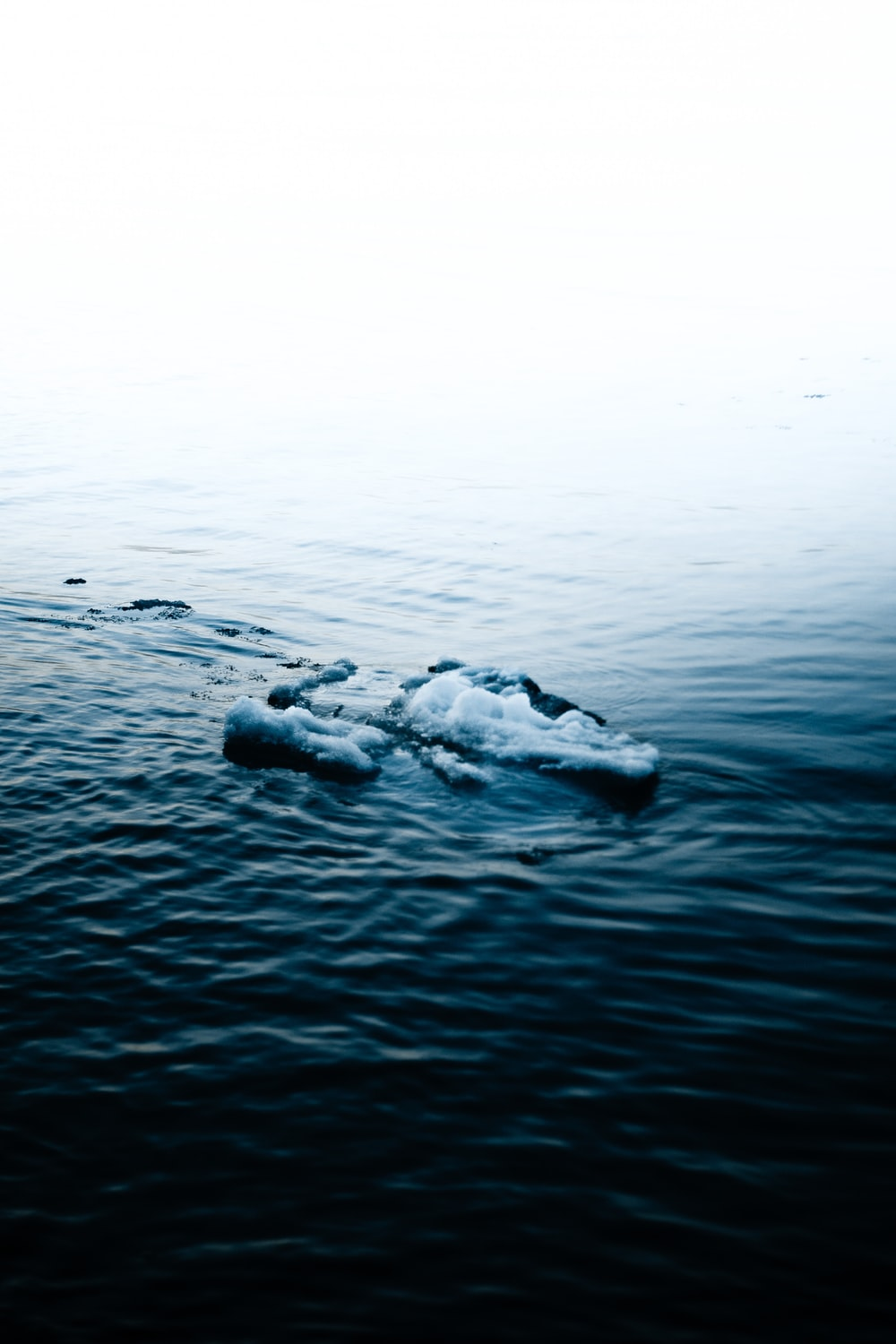 black rock on body of water during daytime