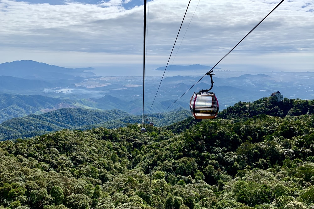 brown cable car over green mountains during daytime