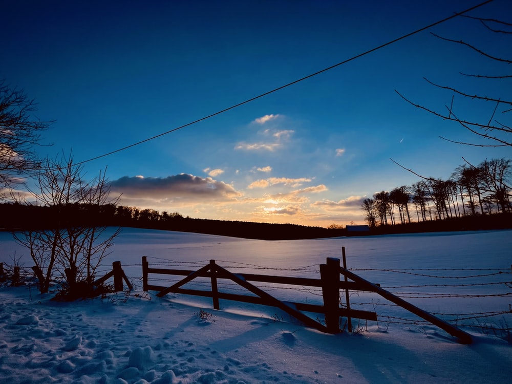 brown wooden fence on snow covered ground during sunset