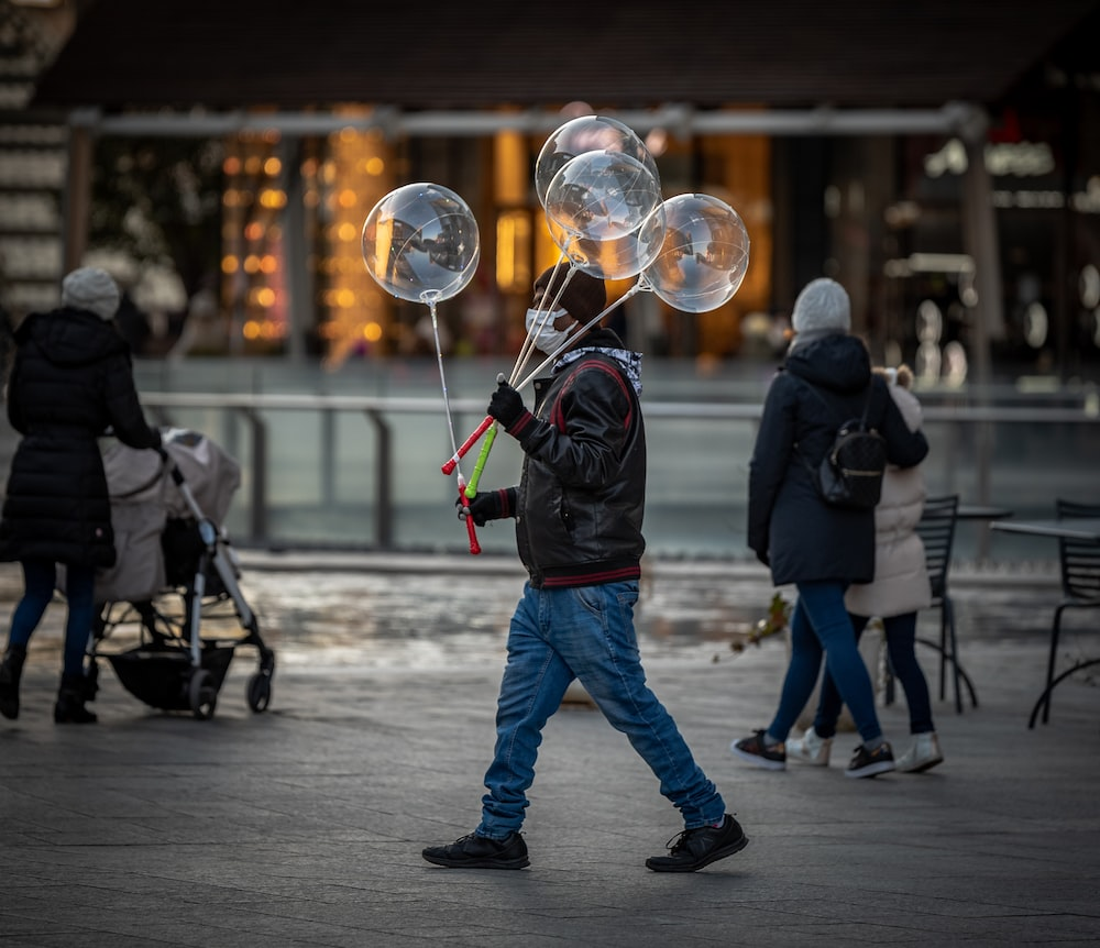 man in black jacket and blue denim jeans holding a bubble stick