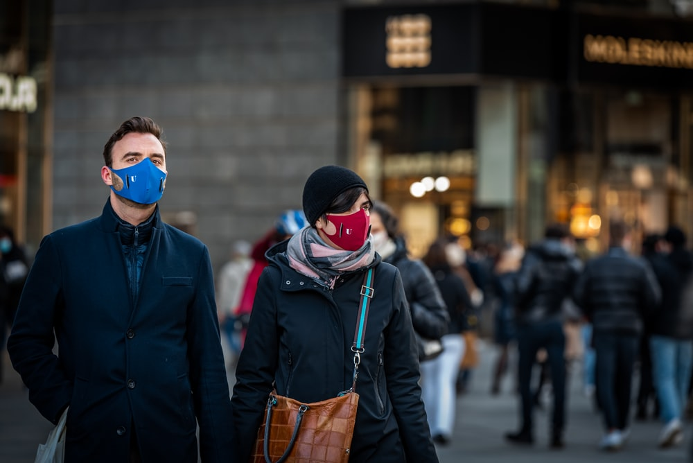 person in black jacket wearing blue mask and white mask