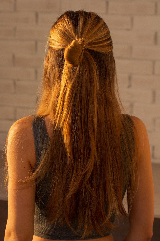 woman in black tank top with brown hair tie