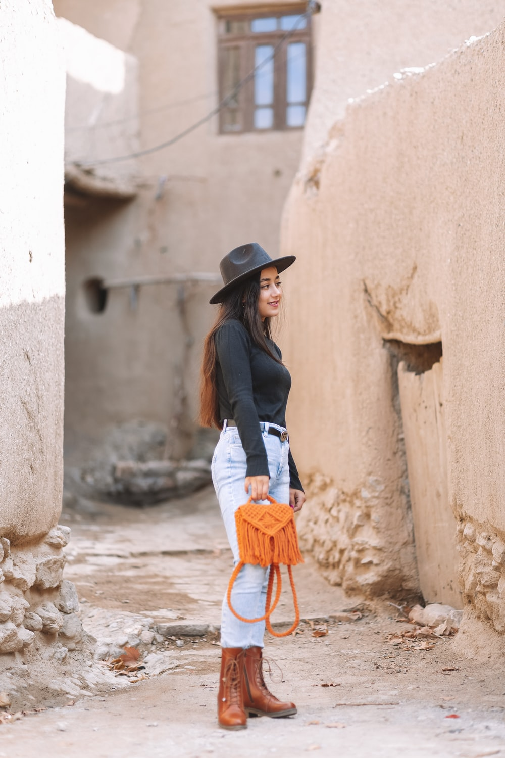 woman in black long sleeve shirt and blue denim jeans wearing black hat standing beside concrete