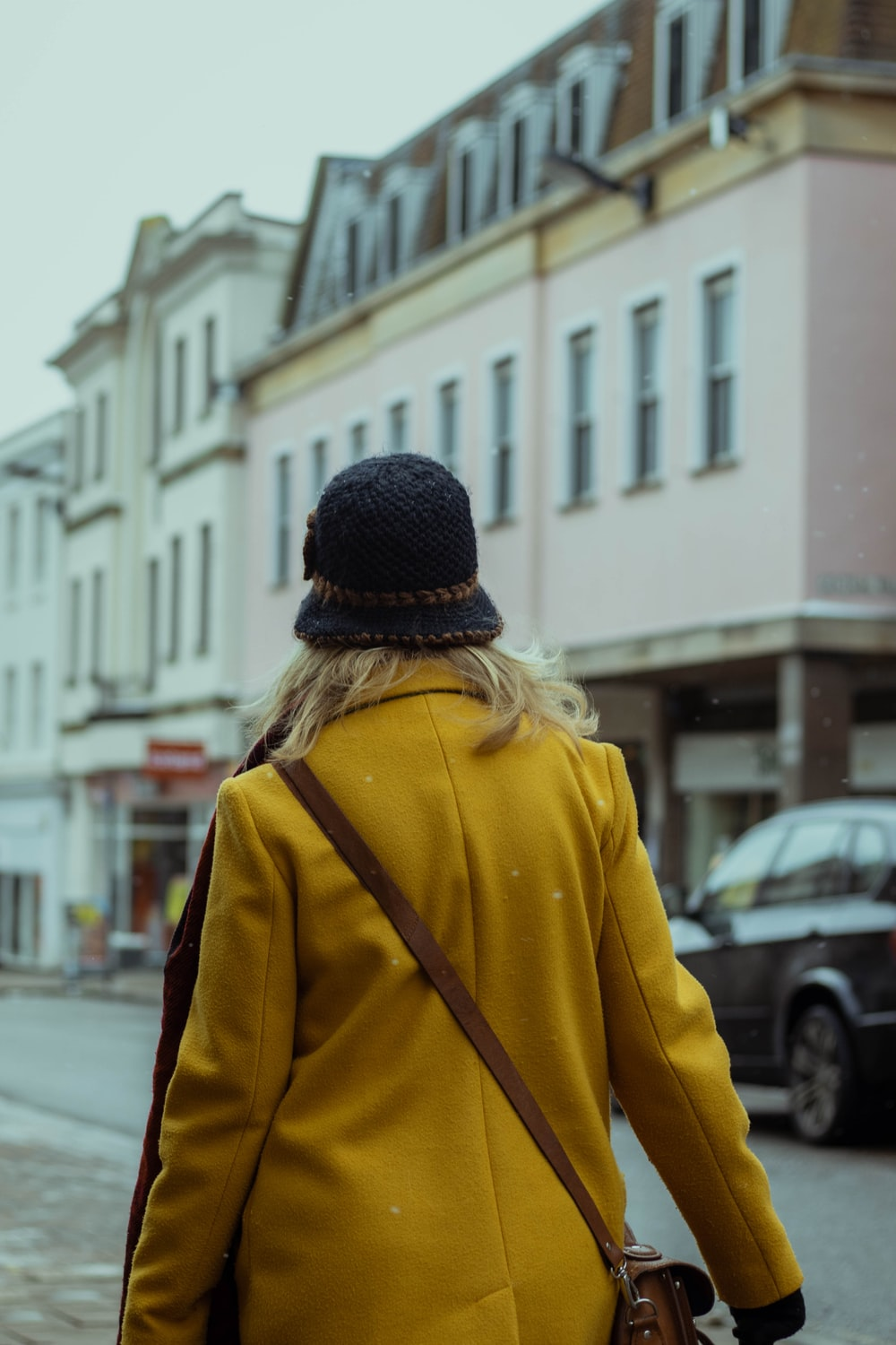 woman in yellow jacket and black knit cap walking on street during daytime
