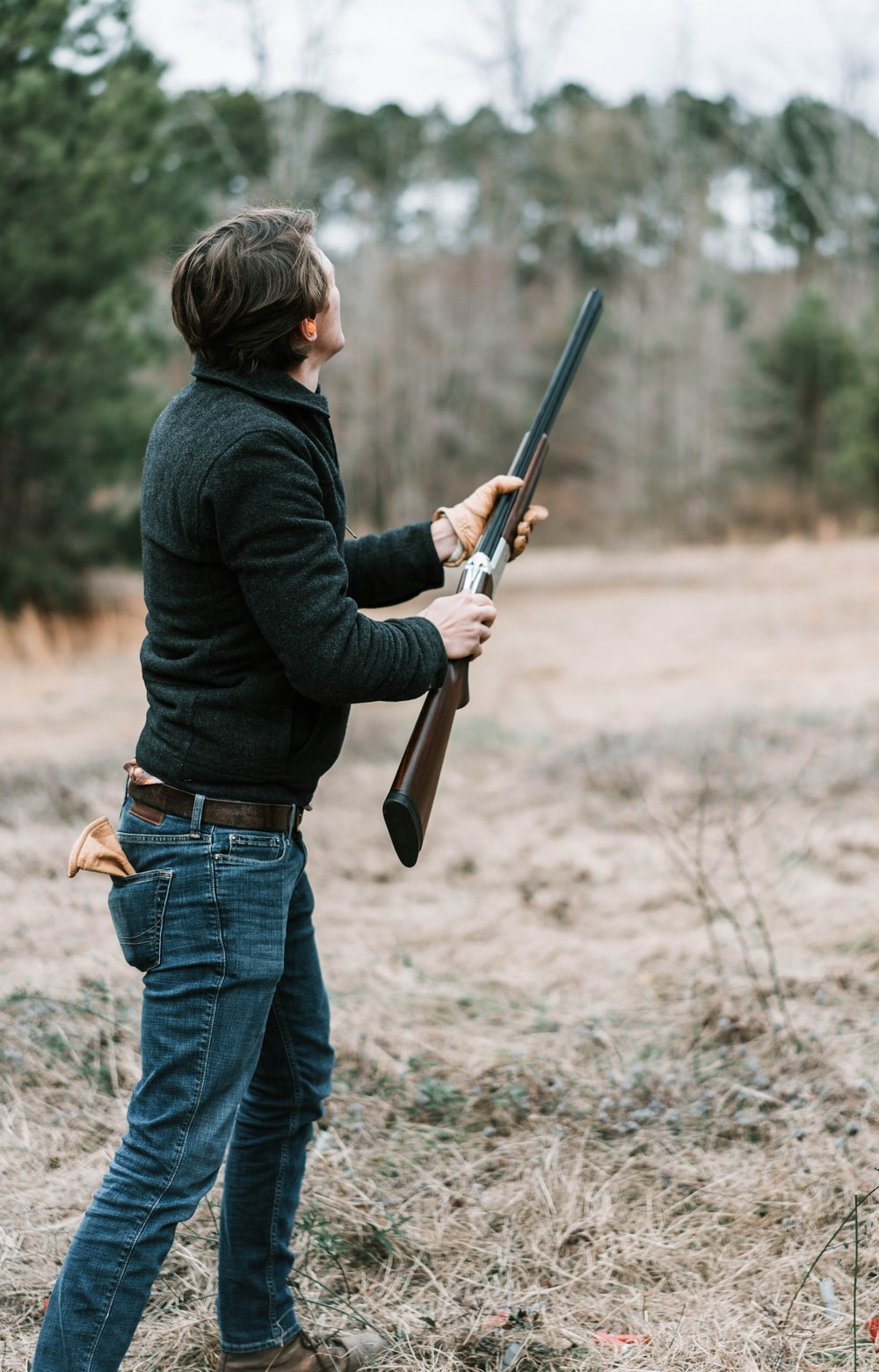 man in black jacket and blue denim jeans holding brown rifle