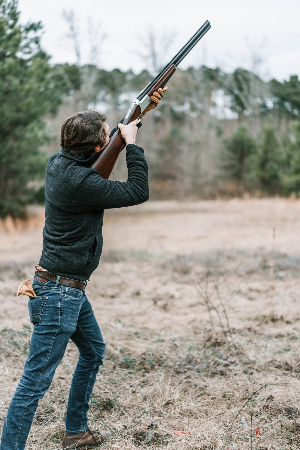 man in black long sleeve shirt and blue denim jeans holding brown rifle