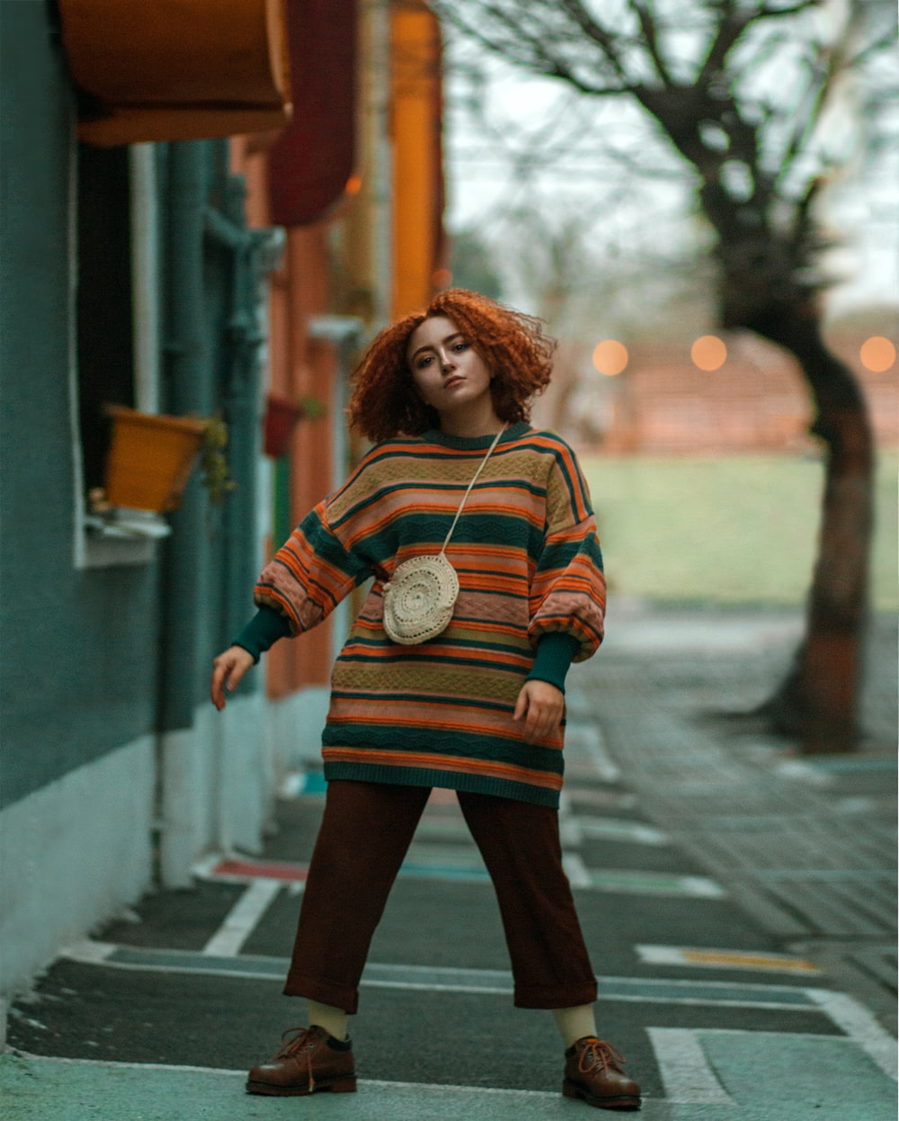woman in white and brown striped long sleeve shirt and black skirt standing on sidewalk during