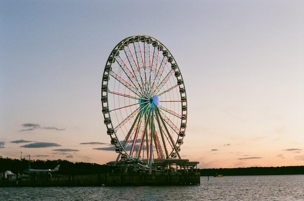 ferris wheel near body of water during sunset