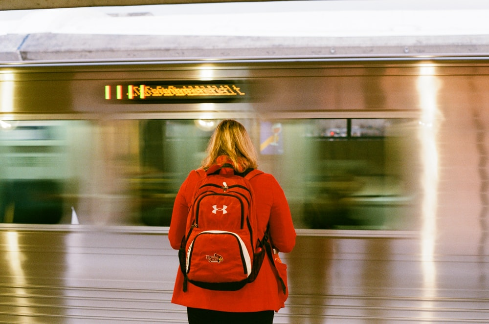 woman in red long sleeve shirt standing in front of train