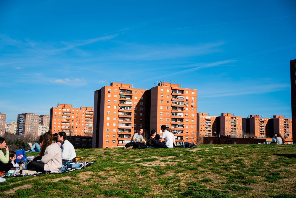man in white shirt sitting on green grass field near city buildings during daytime