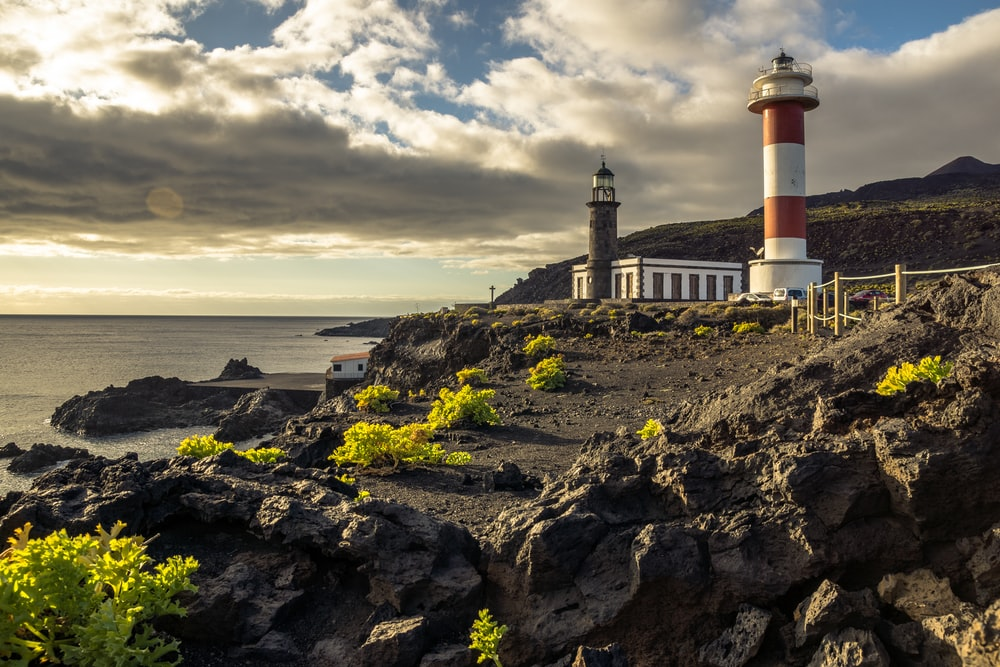 white and red lighthouse on rocky hill near sea under cloudy sky during daytime