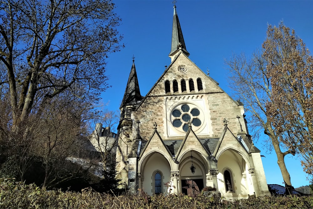 white and brown church near bare trees under blue sky during daytime