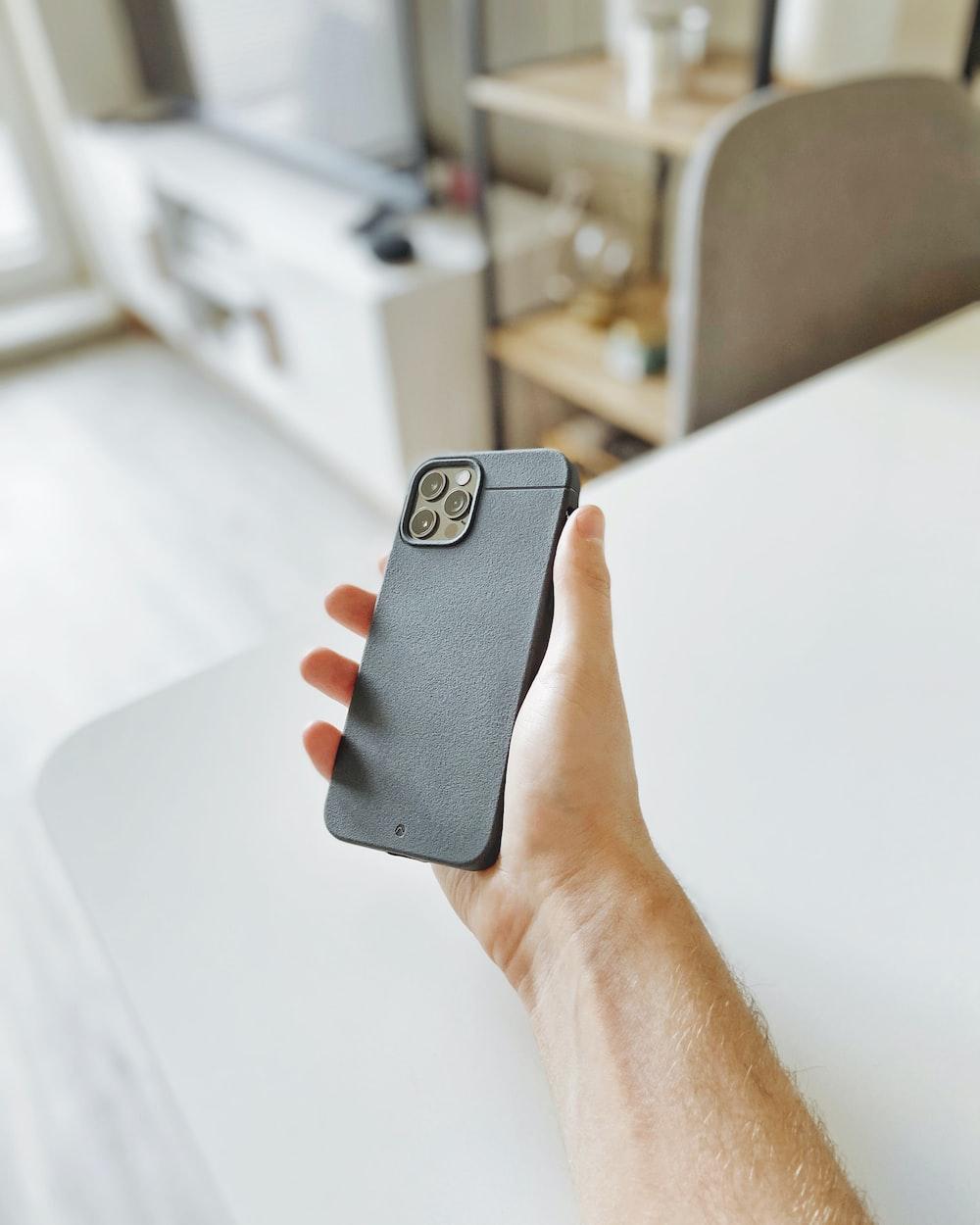 person holding black smartphone case