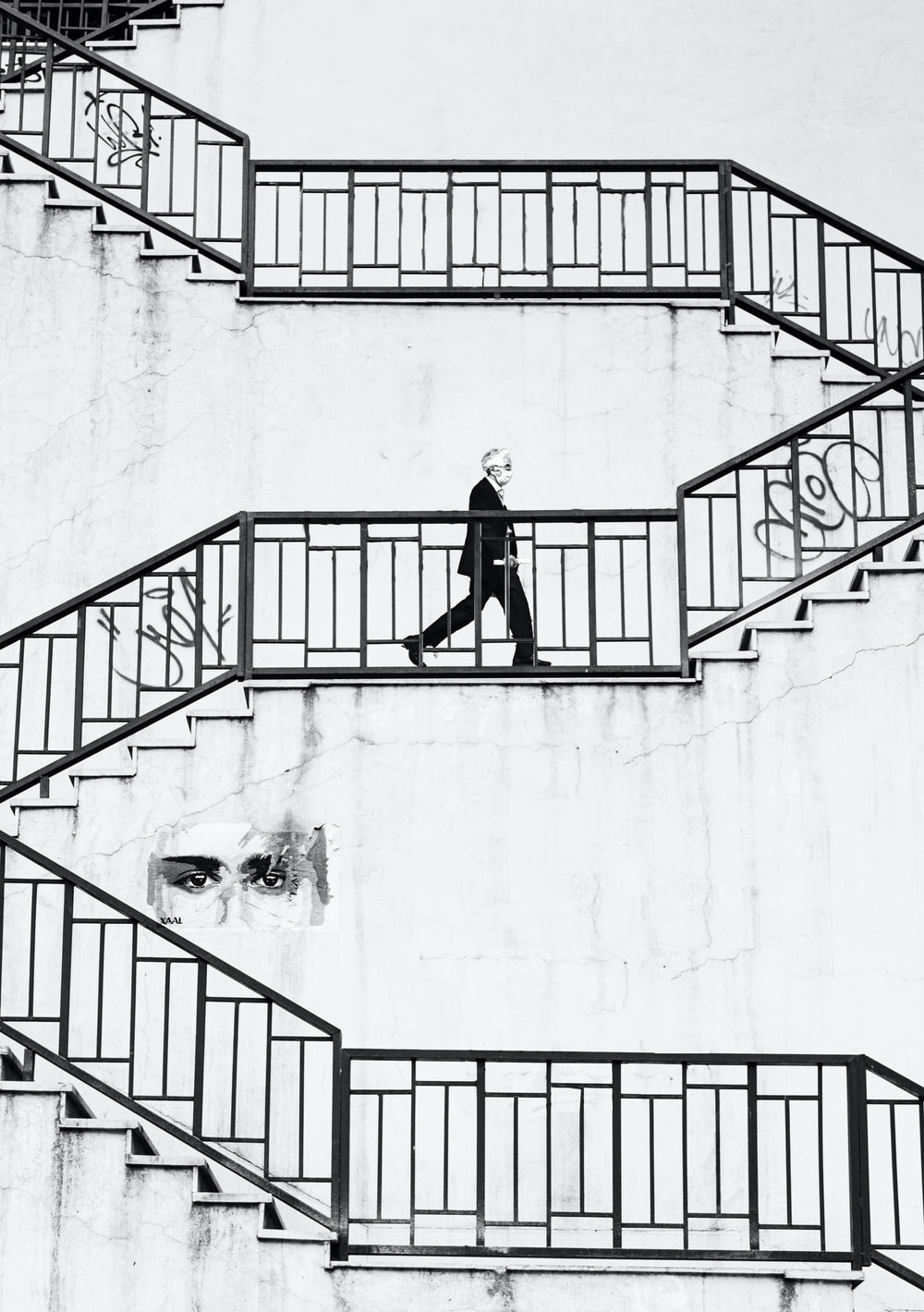 man in black jacket and pants walking down on stairs