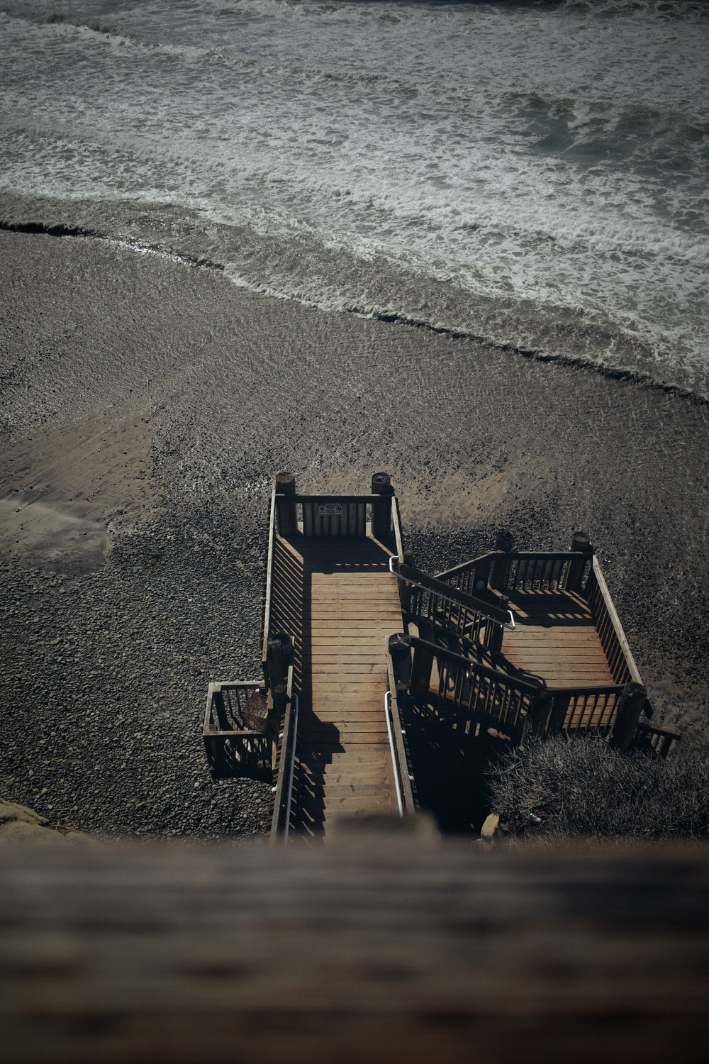 brown wooden chairs on beach shore during daytime