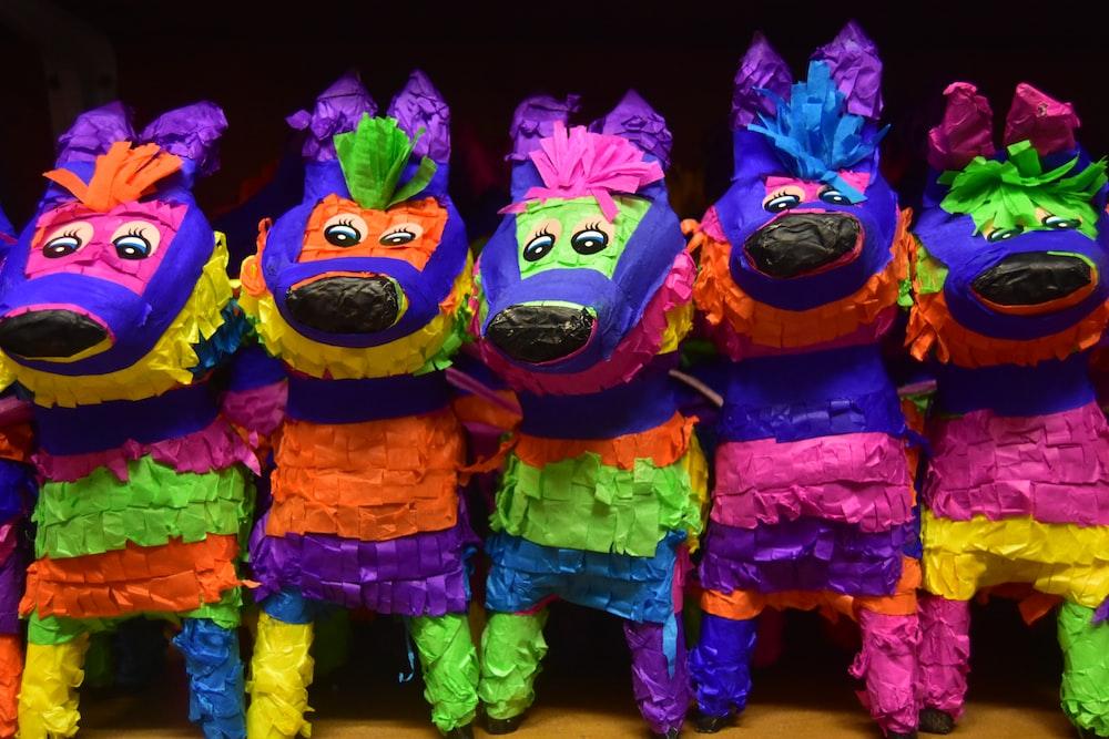 purple green and orange animal plush toys